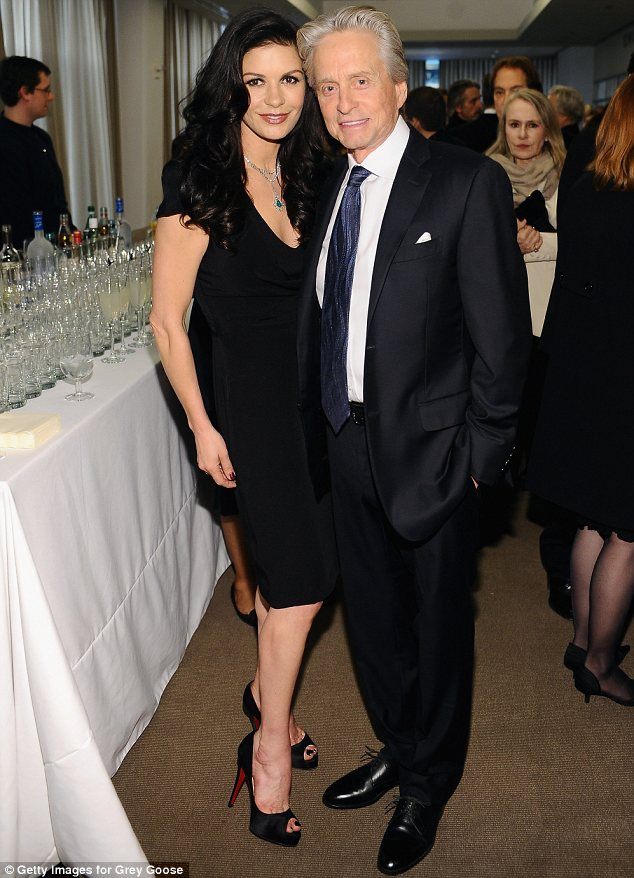 Keeping close: The pair cuddled up by the bar. Catherine chose a little black dress while Michael looked suave in a suit