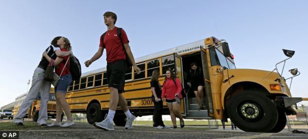 High school students hug as they arrive for classes at a temporary facility in nearby Waco
