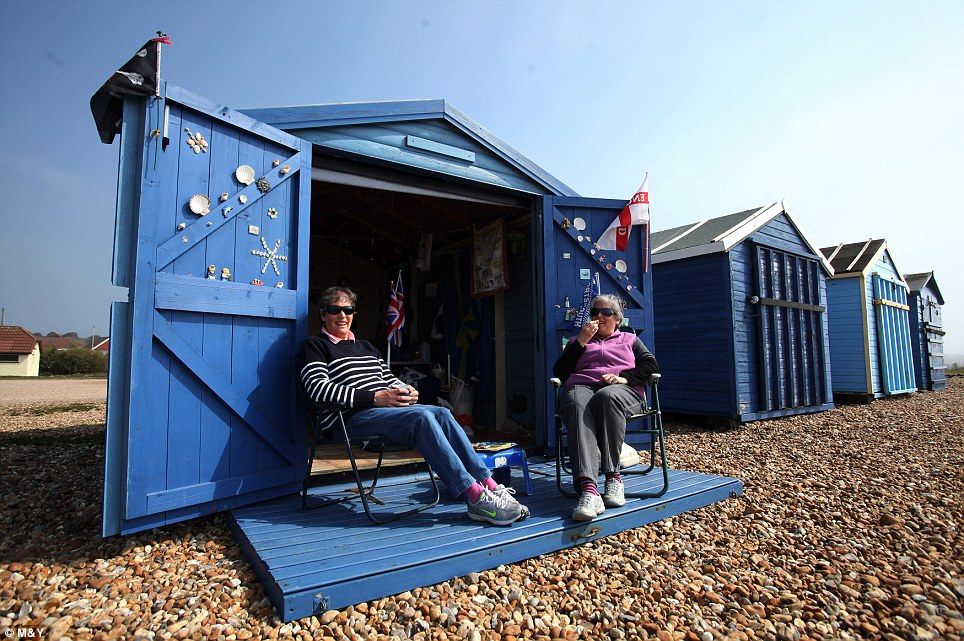 Warm: Sisters Jane Bailey, 62, and Corinne Goater, 63, sit outside their beach hut at Hayling Island, Hampshire, today