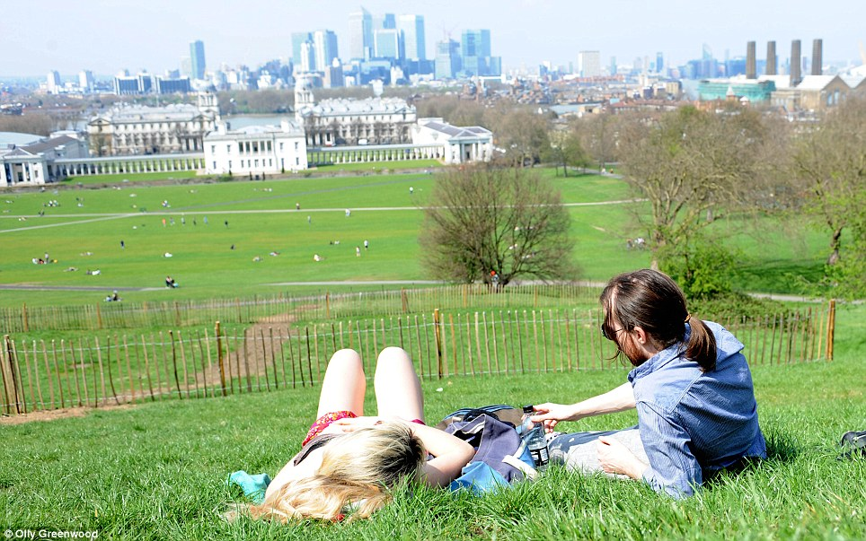 Beautiful day: A couple enjoy the weather in Greenwich park, central London, today