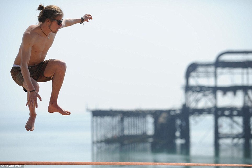 Very high jump: The man leaps into the air while balancing on a cord above Brighton Beach today