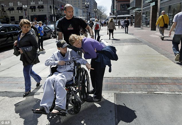 Return: Aaron Hern points to the site of the first Boston Marathon bombing to his mother, Katherine, while his father, Alan, wheels him down Boylston Street in Boston's Copley Square