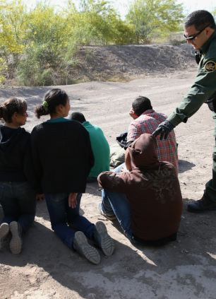 U.S. Border Patrol agents detain undocumented immigrants near the U.S.-Mexico border on April 11, 2013 near Mission, Texas
