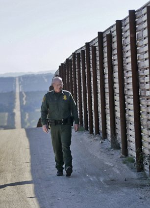 In this Monday, March 25, 2013 photo, Border Patrol agent Richard Gordon, a 23-year veteran of the agency, walks the border fence in the Boulevard area east of San Diego looking for signs that reveal movement of illegal immigrants