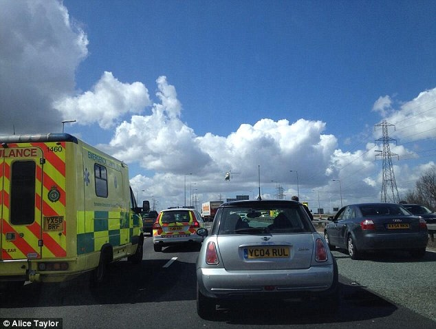 Accident: The air ambulance can be seen landing (centre) as paramedics treat the injured at the scene of the crash today. Picture provided by Alice Taylor