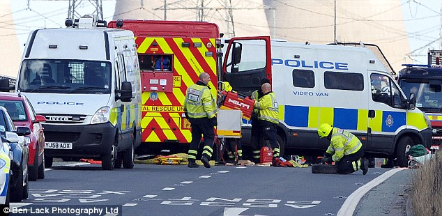 Emergency operation: Police and fire services work on the scene on the M62 in West Yorkshire today