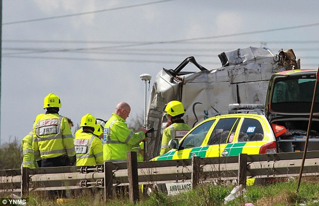 Wreckage: The damaged minibus on the M62 today. One woman has died and 20 others have been injured
