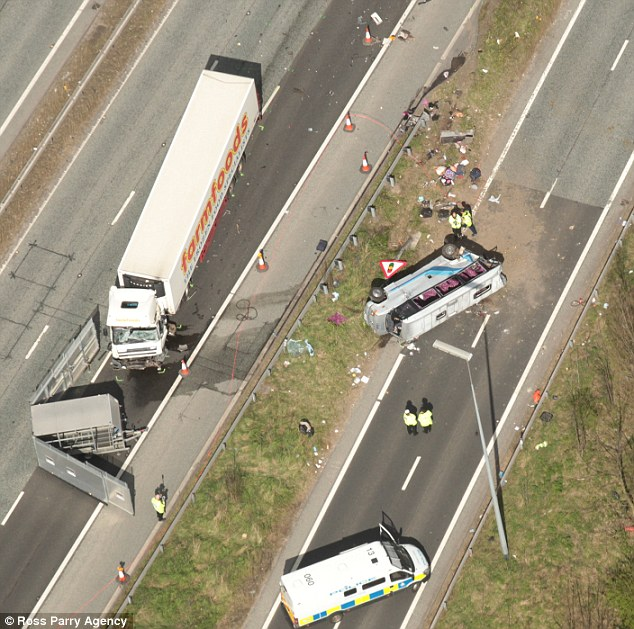 Wreckage: The minibus can be seen on its side. It appears to have collided with the lorry some distance up the road and skidded onto the slip road (right)