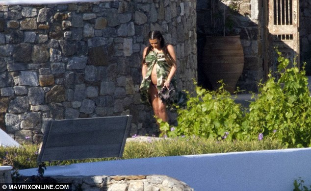 Mother care: Kim took small steps as she carefully walked from the building down towards the beacj