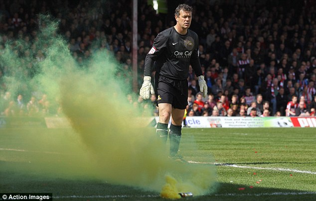 Smoke bomb: Doncaster goalkeeper Neil Sullivan looks at a smoke bomb that's been thrown by a Brentford fan