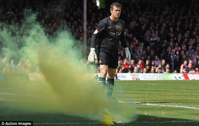Party's started: Neil Sullivan watches after a flare was thrown on the pitch