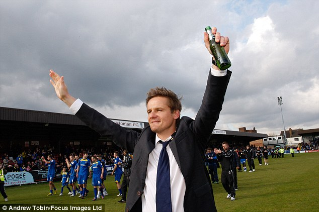 Staying up: Wimbledon manager Neal Ardley celebrates after the whistle with a hard-earned beer
