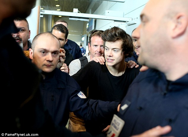 Holding on: One of Harry's team keeps a hand on his shoulders as the French police force take him out of the airport
