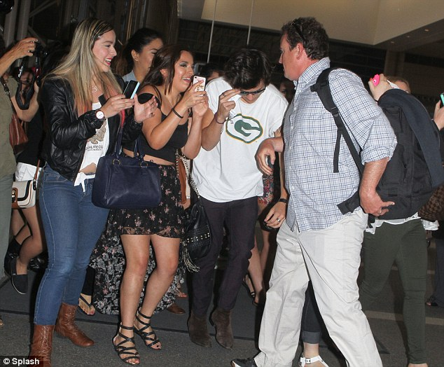In demand: The teen pop sensation was mobbed by a plethora of female fans as he arrived to catch his flight