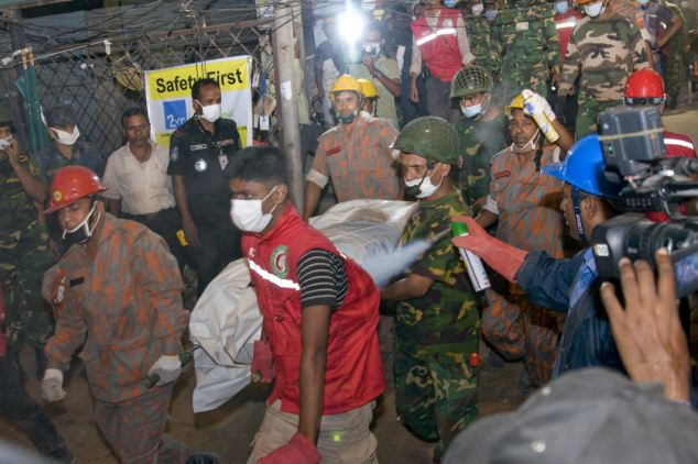 Tragedy: Rescuers carrying out a dead body from the rubble this evening, almost 92 hours after the collapse