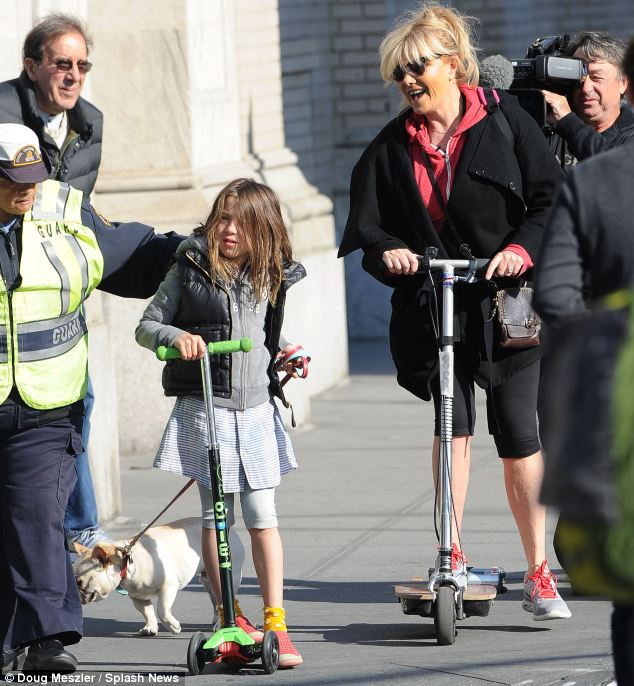 Double-fisted: The little scholar held on to her scooter with one hand and guided her pet pooch with the other while Deborra-Lee looked on