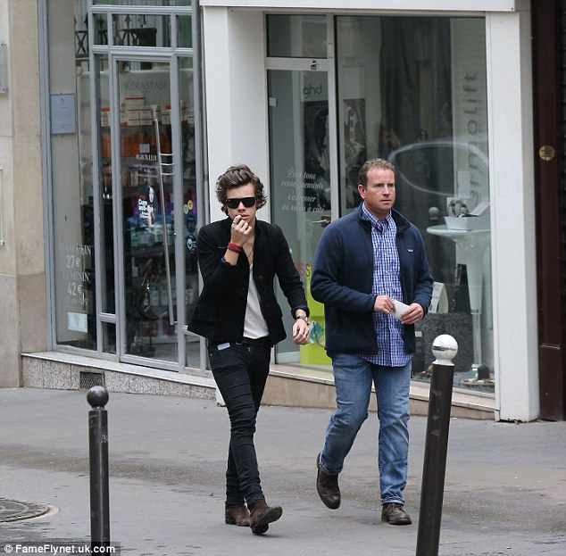 Not blending in: Harry looked instantly recognisable with his mop of dark hair as he took a daytime stroll