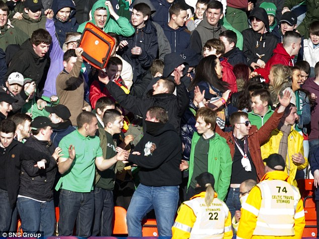 Chaos: A Celtic fan holds up a broken seat in the direction of the stewards