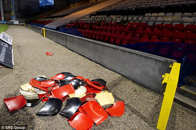 Mess: Broken seats lie on the side of the pitch at full-time