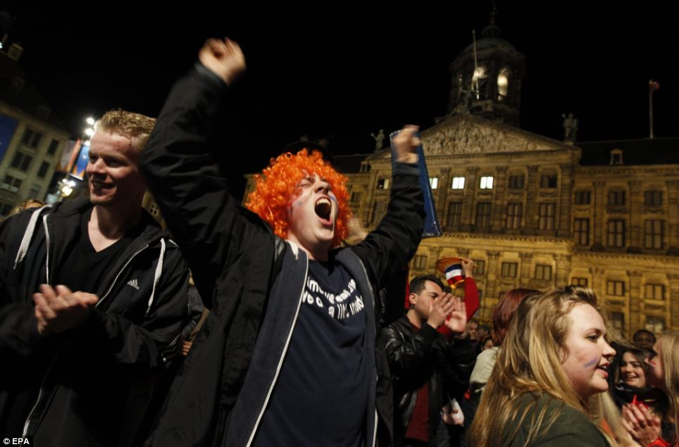 Visitors garther in front of the Royal Palace at the Dam Square on the eve of the upcoming investiture of the country's new King, in Amsterdam, The Netherlands