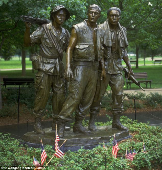 Heroes: American flags stand at the base of a statue of American Soldiers of the Vietnam War in D.C.
