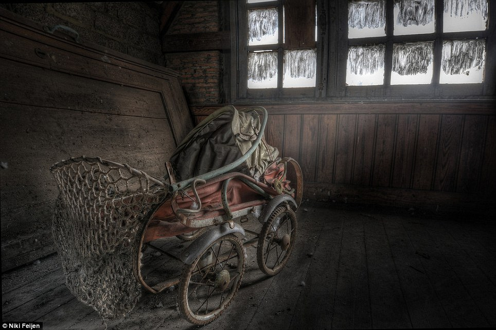 Remains of a life: An old-fashioned baby carriage stands before a smeared window in an empty building that once housed a young family
