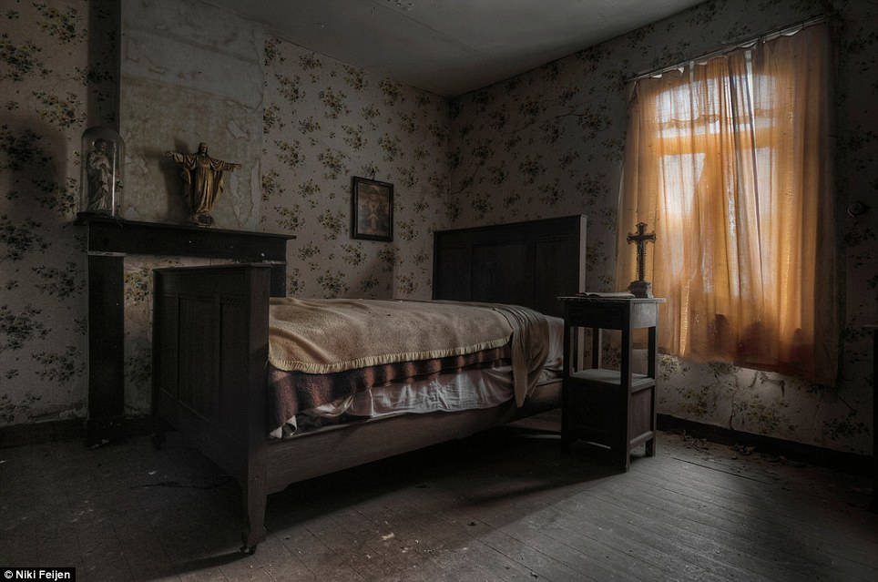 Religious: Layers of blankets remain on the bed in the empty farmhouse, which is still surrounded by crosses and statues of Jesus belonging to its former owner