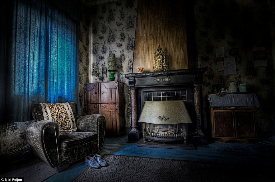 Forlorn: A pair of shoes sit in front of an empty armchair and ornaments remain above the fireplace in this abandoned home
