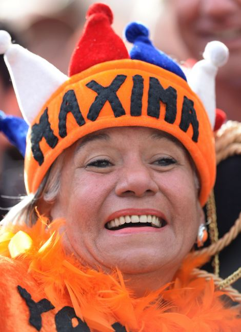 "A woman wears a hat reading ""Maxima"" as she waits on Dam Square"