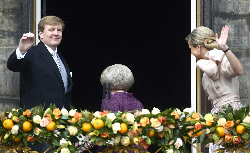 Bowing out: Princess Maxima steps back inside leaving the new King and Queen on the balcony to the delight of the crowd