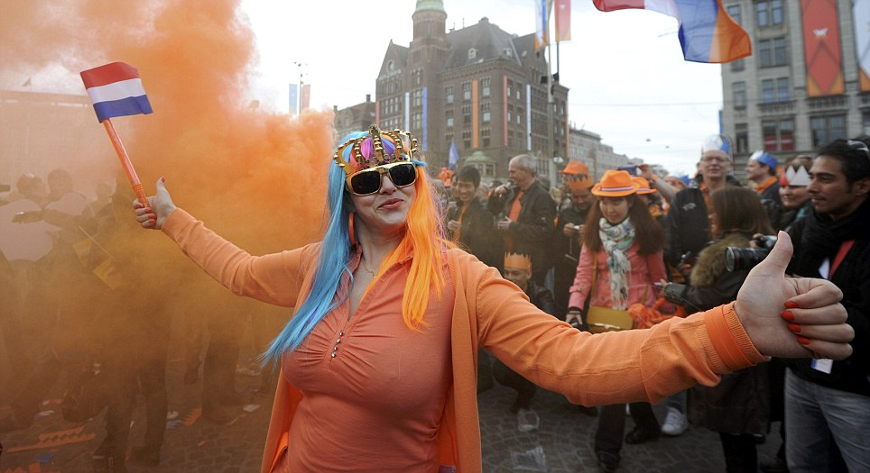 Celebrations: A woman wearing orange and sporting a blue and orange wig topped by a crown waves the Netherlands flag as she poses in Dam Square