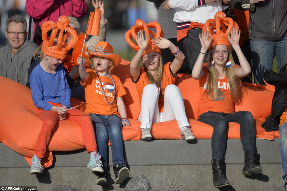 Love and support: Dutch children dressed in orange - the royal colour of the Netherlands - cheer as King Willem-Alexander and his family go past