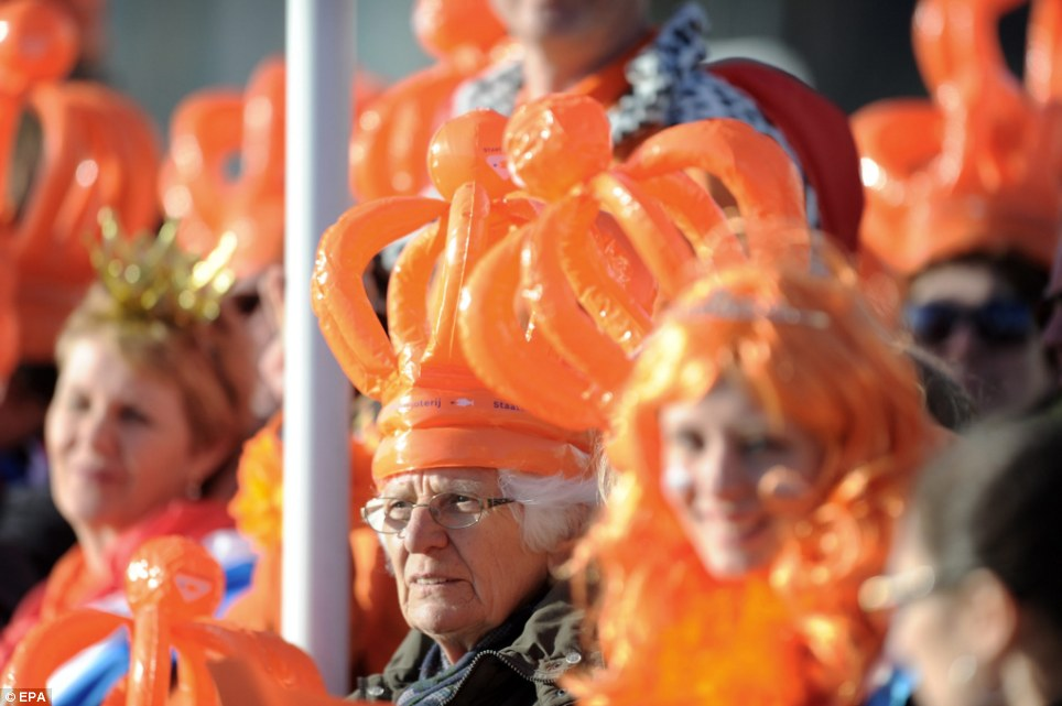 Dutch pride: Fans of the Royal family in orange attire gather on the banks of IJ river to get a glimpse on their new king