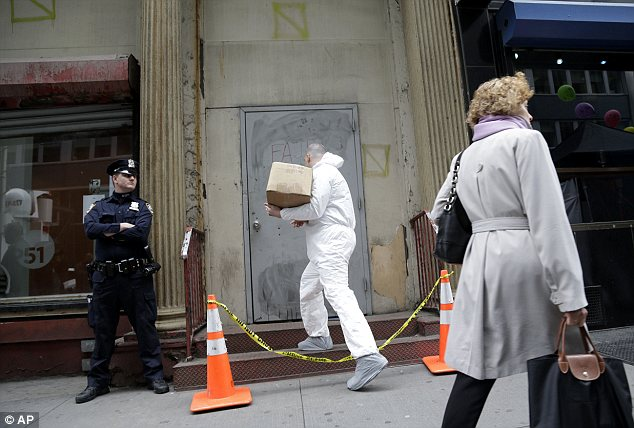 Work: An official in a protective suit enters the site where the plane part was discovered, as an NYPD officer stands guard