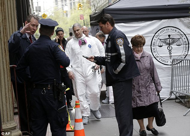 Investigation: Police and officials from the New York City medical examiner's office are seen in the area where a plane part was found last week, just blocks away from the World Trade Center site