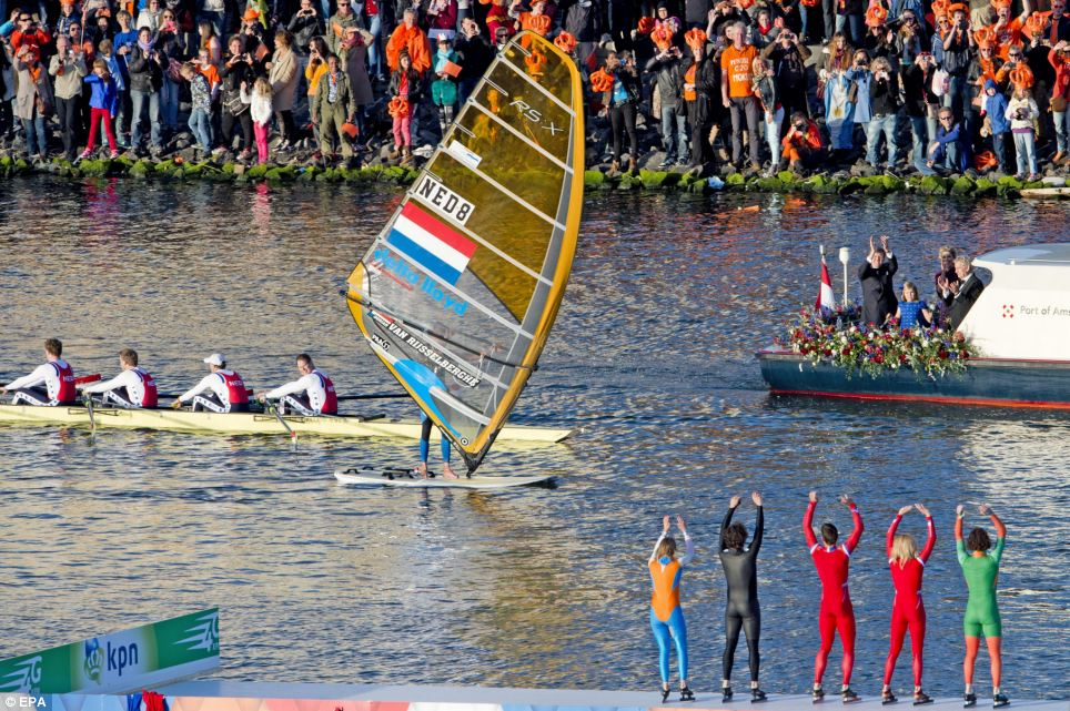 King Willem-Alexander and Queen Maxima wave to spectators and performers during their boat trip on the Ij river in Amsterdam