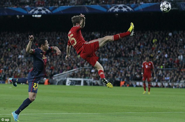 Up for a challenge: Bayern's Thomas Muller attacks the ball in front of Barcelona's Adriano