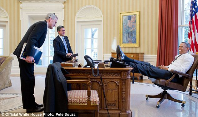 Stretching out: Obama grins with his feet on the table