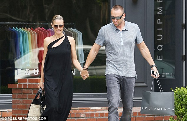 United front: Heidi smiled as she held her bodyguard boyfriend's hand after they bought a few things from clothing store Equipment