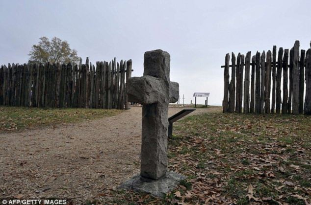 A stone cross marking the grave of a 17th century British settler is seen at the archaeological site of Jamestown