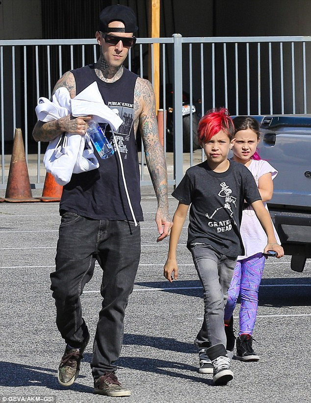 Coming prepared: The Blink-182 drummer carried the kids' uniforms as well as a supply of water
