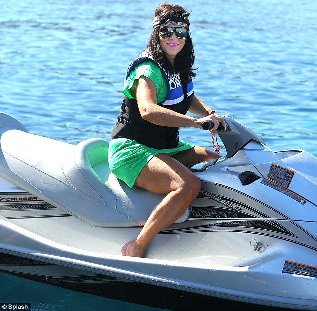 Spitting image: Kris looked more like her daughter Kourtney than herself as she took to the waves in the hair piece