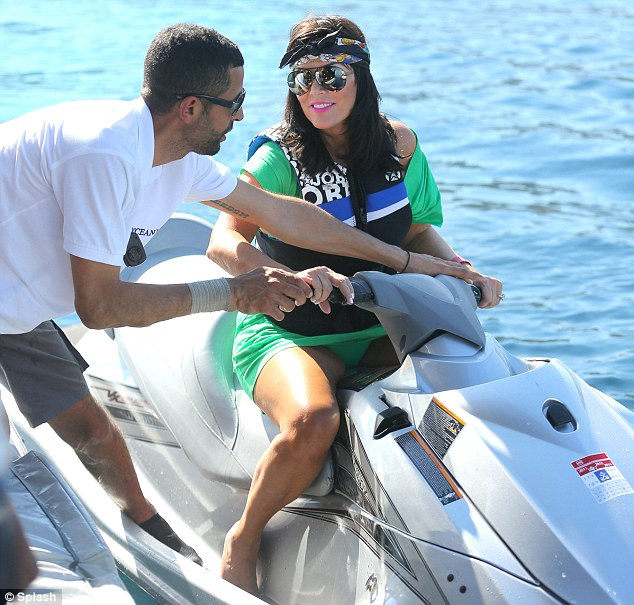 Glamorous: Kris's look was rather over the top for jet skiing as she was also wearing bright pink lipstick