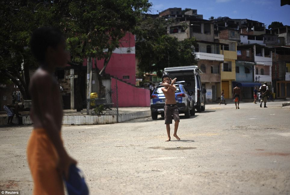Starting young: A boy makes a double gun gesture as he plays on the street of the Nordeste de Amaralina slum complex as a policeman, back right, patrols the area