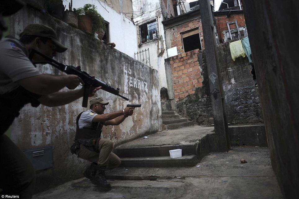 Alert: Armed police react to a perceived threat as they prowl through the Nordeste de Amaralina slum in search of gangsters