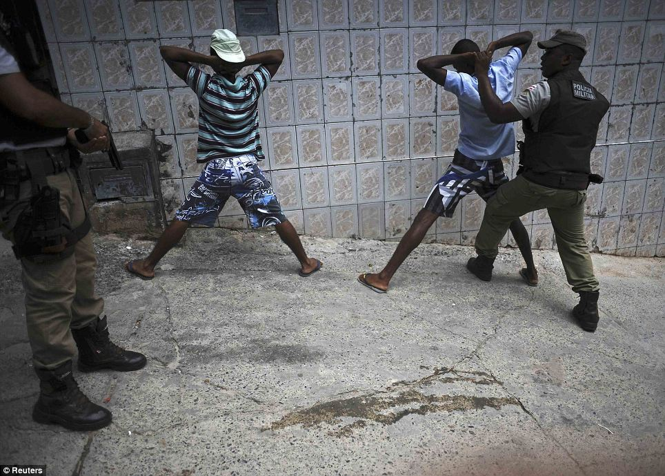 Taking no chances: Police search youths for weapons and drugs while on patrol in the Nordeste de Amaralina slum complex in Salvador, Bahia State