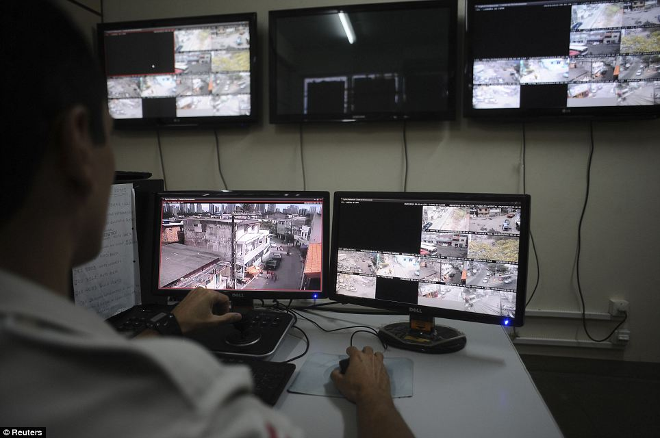 Under surveillance: A police officer watches live security cameras aimed at different points of the city where violence is common, at a command centre in Salvador