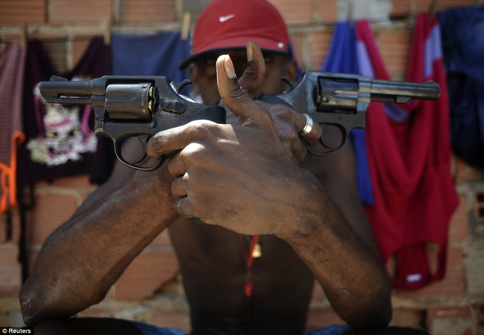 A Brazilian drug dealer nicknamed Pilintra, 26, poses with with two pistols