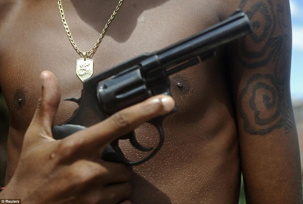 Still just a boy: Giant, 17, poses with his gun and his medallion of St George. Brazilian drug gangs regularly recruit minors, who are subject to lesser sentences under the country's penal code