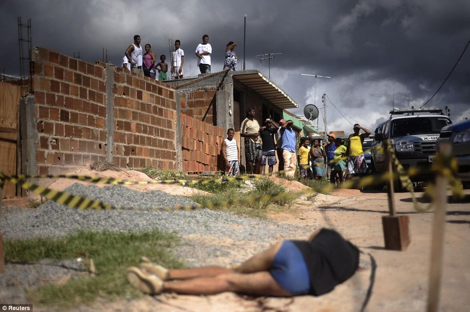 Residents stare at the body of a woman shot in the head in the Sao Cristovao slum